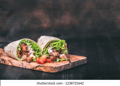 Tortilla wraps with fresh ingredients on a wooden background