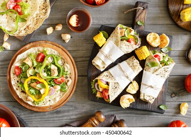 Tortilla wraps with grilled chicken fillet and grilled vegetables on a wooden table. Top view. Outdoors Food Concept