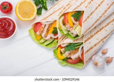 Tortilla wraps with grilled chicken and fresh vegetables on a wooden table. Mexican fast food background. Top view.
