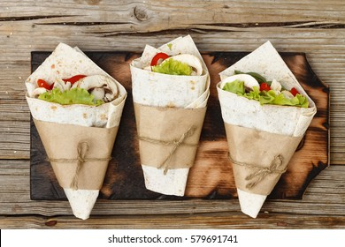 Tortilla wraps with grilled chicken or vegetarian tarteel of fresh vegetables on a wooden background. View from above. filling on pita bread / lunch snacks