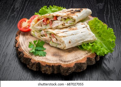Tortilla wraps with grilled chicken or vegetarian tarteel of fresh vegetables on a wooden background. View from above. filling on pita bread lunch snacks