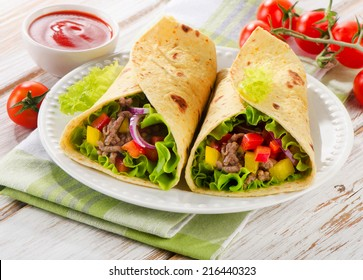 tortilla wraps with meat and fresh vegetables on white plate. Selective focus