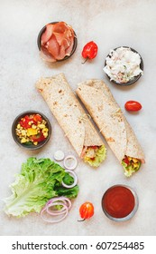 Tortilla wraps sandwiches with fresh various ingredients. Top view, blank space