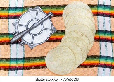 Tortillas circles and traditional press utensil for cooking it on colorful textile background.