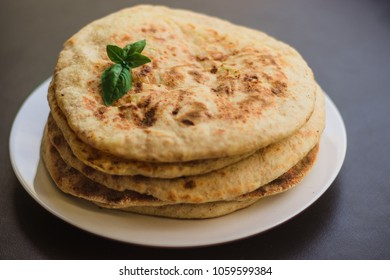 tortillas with potatoes, pita, chapati, decorated with a leaf of basil, on a black background, oriental food