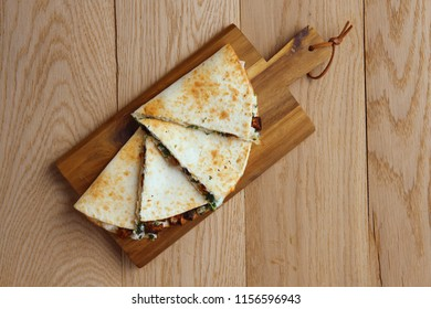 Tortillas stuffed with meat, vegetables and cheese on wooden plate