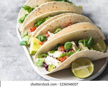 Tortillas with vegetables and white fish. Avocados, tomatoes, red onions and cod pieces sprinkled with sesame and lime juice in tortillas. Mexican food.