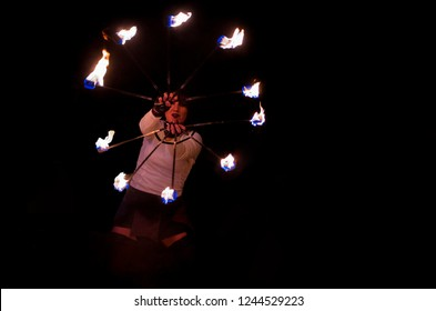Tortona, Italy - November 22 2018: front view of a professional fire juggler girl performing at night with two fire fans
