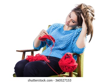 tortured young girl in a blue sweater sits on a chair with a red ball of yarn and knitting a scarf and Spitz. Tired. White background. Isolate