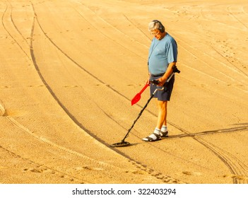 Tossa de Mar, Spain - September 12, 2015: Man looking for lost jewelry with metal detector on the beach of Tossa de Mar. Famous tourist resort on the Mediterranean coast.