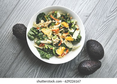 Tossed Asian salad with mangoes, avocados, spinach, edamame beans, ramen, almonds, and carrots.