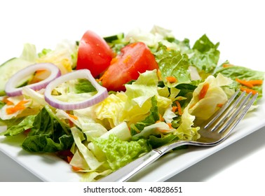 Tossed salad with lettuce, tomato, cucumber, onion, carrot on a white plate with a fork