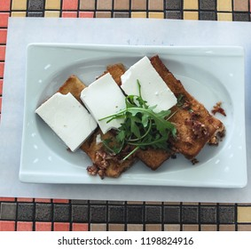Tost bread slices poach fried with fresh cow cheese and rocket leaves served in plate. Selective focus