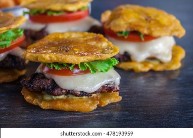 Tostones burger, Crushed fried plantains with beans, onion, tomato and white cheese on wood table.