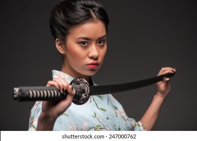 Total concentration. Side view portrait of young beautiful Japanese woman in kimono looking aggressively at camera and holding katana sword while standing against grey background