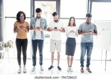 Total ignorance. Full length shot of millennial employees standing in a row and ignoring each other while focusing their attention on screen of their phones.