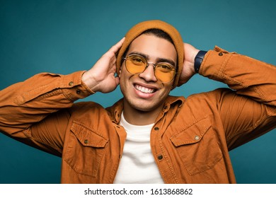 Total relax concept. Portrait of happy smiling mixed race man in yellow outfit, wearing hat and glasses, looking at camera and holding his hands behing his head, isolated over blue studio background.