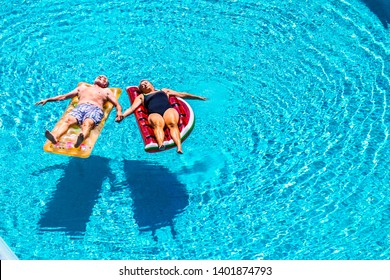 Total relax for happy mature senior retired people lay down on coloured lilos inflatable mattress on blue clear water of swimming pool in summer time - enjoying lifestyle and vacation