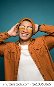 Total relax. Portrait of happy smiling mixed race man in yellow outfit, wearing hat and glasses, holding his hands behing his head, isolated over blue studio background.