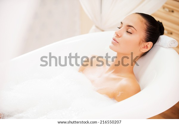 Total relaxation. Attractive young woman keeping eyes closed while enjoying luxurious bath