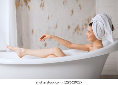 Total relaxation. Beautiful young woman with her brow hair tucked under the towel showing her slender bare leg while lying in bathtub over light background