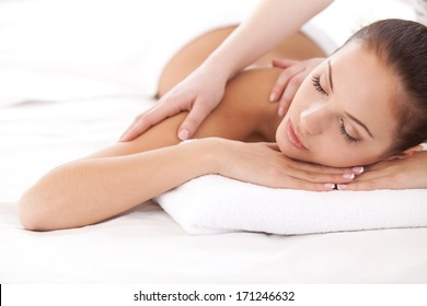 Total relaxation. Beautiful young woman lying on front and looking at camera while massage therapist massaging her shoulders