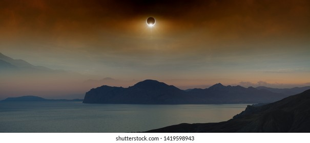 Total solar eclipse in dark red sky above sea and mountains, mysterious natural phenomenon when Moon passes between planet Earth and Sun