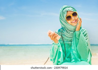 total sun protection concept: pretty girl on a beach wearing traditional muslim costume