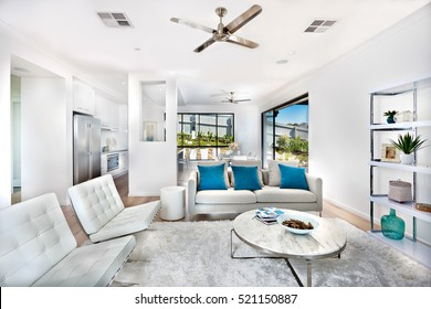 Total white living room decoration, interior with the kitchen of a luxury house expressing the color of white within same color walls and furniture. There are round tables.