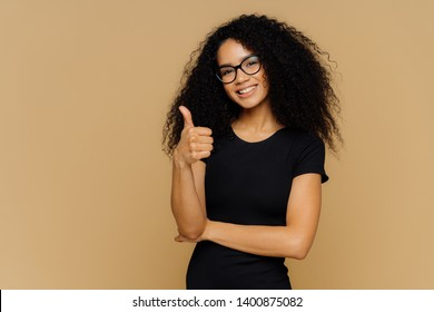 I totally agree. Good looking satisfied Afro American woman keeps thumb up, dressed in casual black t shirt, has crisp hair, wears spectacles, models over brown background. Body language concept