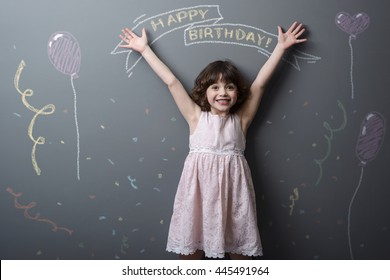 Totally happy little girl with adorable smile and rised hands looks in the camera. Pictured with chalk congratulations with birtday, confetti and toy balloon on neutral background.