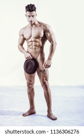 Totally naked male bodybuilder hiding genitals with hat, looking at camera smiling, on light grey background.