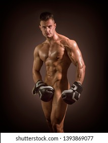 Totally naked male bodybuilder hiding genitalia with boxing gloves, looking at camera, on dark background
