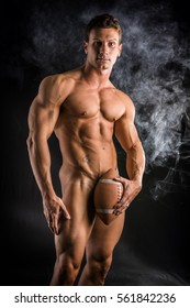 Totally naked male bodybuilder hiding genitalia with american football ball, looking at camera, on dark background