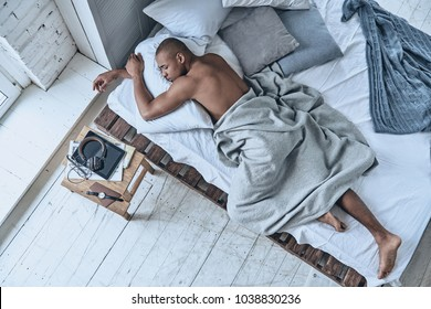 Totally relaxed. Top view of young African man sleeping while lying in the bed at home