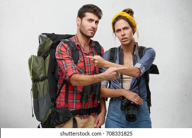 It's totally your fault. Picture of angry male and female hikers or tourists equipped with traveling stuff pointing fingers at each other, blaming one another for getting lost during hiking trip