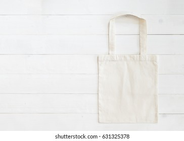 Tote bag canvas fabric cloth eco shopping sack mockup blank template on white wood background