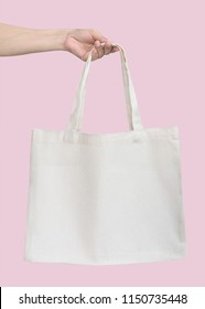 Tote bag canvas white cotton fabric cloth for eco shoulder shopping sack mockup blank template isolated on pastel pink background (clipping path) with woman's  hand holding it.