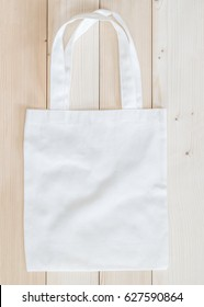 Tote bag fabric cloth shopping sack mockup on white wood, top view