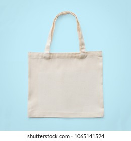 Tote bag mock up canvas white cotton fabric cloth for eco shoulder shopping sack mockup blank template isolated on pastel blue background (clipping path)