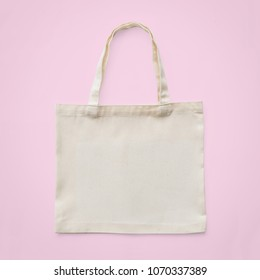 Tote bag mock up canvas white cotton fabric cloth eco shopping sack mockup blank template isolated on pastel pink background (clipping path)