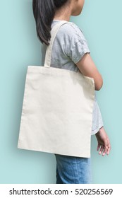 Tote bag mockup cotton canvas fabric texture on girl shoulder (clipping path) in white cream color isolated on blue background