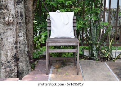 A tote bag place on a wooden chair in outdoor.