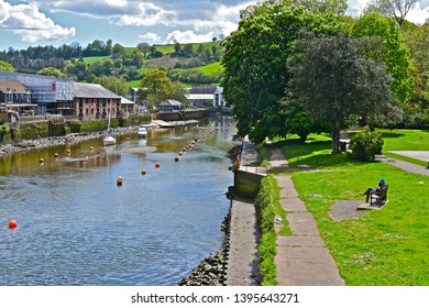 Totnes, Devon / England - 5/4/2019: A peaceful view of the River Dart as it winds it's way through the town centre of Totnes. Background of gently rolling wooded hills. Yachts moored in river.