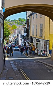 Totnes, Devon / England - 5/4/2019: A pretty street view looking down the hill from through the archway building in High Street, towards shoppers in the busy Fore Street in Totnes town centre.
