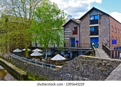 Totnes, Devon / England - 5/4/2019: The rear garden of the Waterside Bistro & bar in Totnes. People enjoying a drink outdoors in the beer garden overlooking the River Dart.