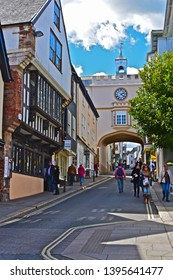 Totnes, Devon / England - 5/4/2019: A street view of shops at top end of Fore Street in Totnes town centre showing the ancient building built over the high Street and featuring clock & tower.