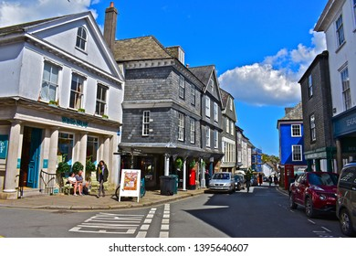 Totnes, Devon / England - 5/4/2019: A view down the High Street in central Totnes at the junction with Castle Street with quaint old buildings crowding the street. Old red postbox & telephone kiosk.