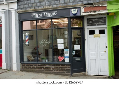 TOTNES, UK - JUNE 26, 2021 Fore Street Barbers hairdressers shop on Fore Street on a cloudy day
