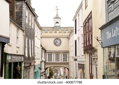 Totnes, United Kingdom - March 26, 2016: Quaint Town Clock. Across the narrow main street of Totnes is a building that connects the two sides of the street. On top is a weather vane and an old clock.